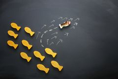 different fish swimming opposite way of identical ones. Courage and success concept. Blackboard background.