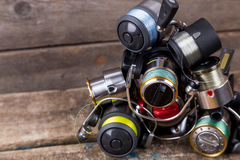 Different fishing reels with line on wooden background stock image