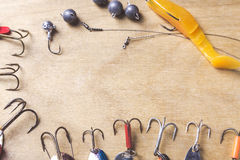 Different fishing tackles and plastic worm on wooden board background Stock Image