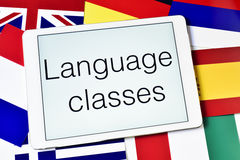 Different flags and the text language classes in the screen of a. The text language classes in the screen of a tablet computer surrounded by flags of different Stock Photography