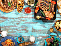 Different food cooked on the grill on blue wooden table Royalty Free Stock Photos