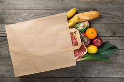 Different food in paper bag on wooden background, close up. Grocery shopping concept, top view stock photos