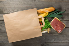Different food in paper bag on wooden background Stock Images