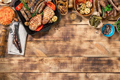 Different foods cooked on the grill on the wooden table. With copy space, grilled steak, grilled sausage and grilled vegetables. Top view Royalty Free Stock Images