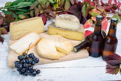 Different French cheeses with a few bottles of beer. And grapes Royalty Free Stock Photos