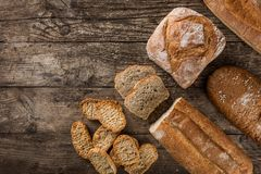 Different fresh bread and spikelets of wheat on rustic wooden background. Creative layout made of bread. Healthy food concept,. Top view, flat lay, copy space stock photography