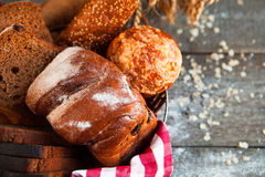 Different fresh bread in wicker basket on rustic table on wooden Royalty Free Stock Images