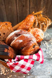Different fresh bread in wicker basket on rustic table on wooden Royalty Free Stock Image