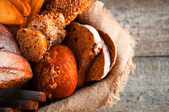 Different fresh bread in wicker basket on rustic table on wooden Royalty Free Stock Photography