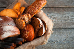 Different fresh bread in wicker basket on rustic table on wooden Stock Images