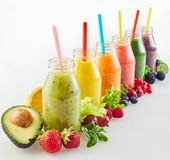 Different fresh fruit smoothies with ingredients. Receding diagonal row of different fresh fruit and vegetable smoothies with colourful ripe ingredients on white royalty free stock photography