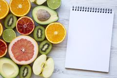 Different fresh fruits with blank notepad on white wooden table, top view. Summer background. Copy space stock photo