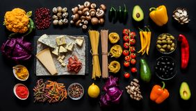 Different fresh ingredients for cooking italian pasta, spaghetti, fettuccine, fusilli and vegetables on a black. Background. Flat lay, top view Stock Image