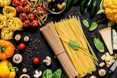 Different fresh ingredients for cooking italian pasta, spaghetti, fettuccine, fusilli and vegetables on a black. Background. Flat lay, top view Royalty Free Stock Photography