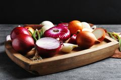 Different fresh onions. On wooden board Royalty Free Stock Image
