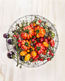 Different fresh tomatoes in a basket on white wooden background top view. Different tomatoes in a basket on white wooden background stock photography