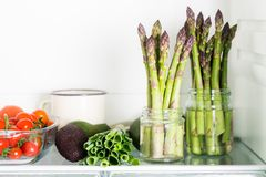 Flavoursome, sweet and tender British asparagus in the fridge. Different fresh vegetables, such as Avocados, Salads and British asparagus in the fridge Royalty Free Stock Photo