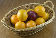 Different Fruit. Wicker basket of oranges and one apple Royalty Free Stock Photography