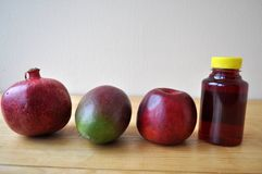 Different fruits and a bottle of juice on a wooden surface royalty free stock images