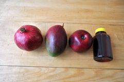 Different fruits and a bottle of juice on a wooden surface stock image