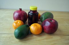 Different fruits and a bottle of juice on a wooden surface stock photos