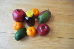 Different fruits and a bottle of juice on a wooden surface stock images