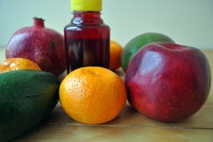 Different fruits and a bottle of juice on a wooden surface royalty free stock photography