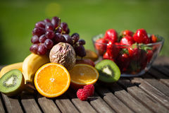 Different fruits with fruit juice on garden table. Different fruits for smoothie, green background Stock Image