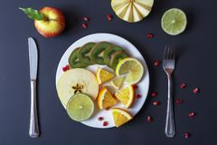 Different fruits on a white plate. With cutlery on a dark background as a diet symbol. Useful dietary food. The recipe for losing weight royalty free stock photos