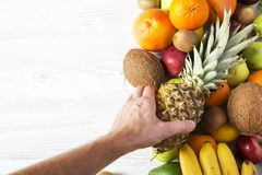 Different fruits on white wooden background. Flat lay. Different fruits on white wooden background. Man`s hand takes a pineapple. Flat lay. Top view. Copy space royalty free stock photos