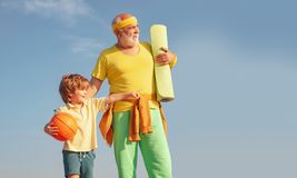 Different generations. Like sports. Joyful old-aged man and cute little boy practicing sport and healthy lifestyle over