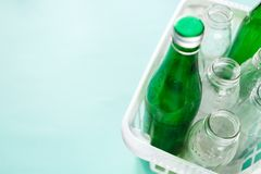 Different glass bottle wastes ready for recycling in white basket on green background. Social responsibility, ecology care stock photography