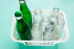 Different glass bottle wastes ready for recycling in white basket on green background. Social responsibility, ecology care royalty free stock image