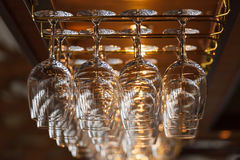 Different glasses hanging over the bar. Soft focus. Royalty Free Stock Photos