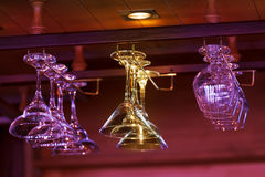 Different glasses hanging over the bar. Soft focus. Royalty Free Stock Image