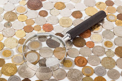 Different gold and silver collector`s coins and magnifying glass Stock Images