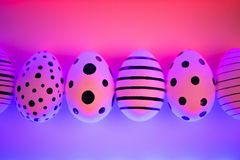Different graphic hand-painted eggs in Proton Purple neon light. stock photography
