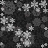 Different gray messy snowflakes on dark Royalty Free Stock Photography