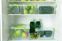 Different green vegetables and fruits in containers. On shelves of refrigerator royalty free stock image