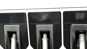 Different guns for pouring gasoline hang in row at the gas station.Gasoline or petrol station gas fuel pump nozzle. Different guns for pouring gasoline hang in a stock video footage