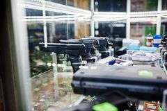 Different guns and revolvers on shelves store weapons on shop ce Royalty Free Stock Photos