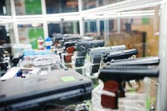 Different guns and revolvers on shelves store weapons on shop ce Royalty Free Stock Photo