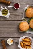 Different Hamburger On Wooden Table With Sauces, Fries And Pickl Stock Image