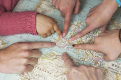 Different hands pointing to Spain in a world map Stock Image