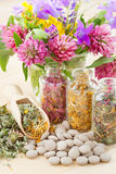 Different healing herbs in glass bottles. Flowers bouquet, tablets, herbal medicine Stock Photos