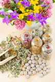 Different healing herbs in glass bottles, flowers. Bouqet in mortar, tablets, herbal medicine, top view Stock Image