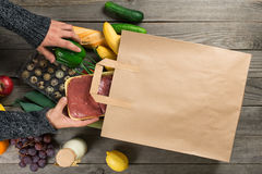 Different healthy food on wooden table with paper bag Royalty Free Stock Image