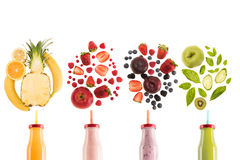 Different healthy smoothies in bottles with fresh ingredients isolated on white Royalty Free Stock Photography