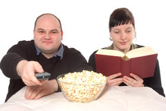Different hobbies. Woman is reading a book while man is watching tv Royalty Free Stock Image