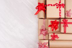 Different holiday gifts with red bows closeup on white wooden background, top view, copy space royalty free stock images